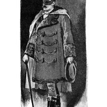 A masked man with a cane stands wearing a frogged coat and a cape