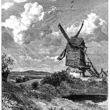 View of a windmill standing in the open countryside with a pond in the foreground