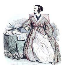 A woman in a dressing-gown is sitting iat a table covered with papers