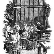 View of a workshop where workers sitting on stools use hammers to craft flatware