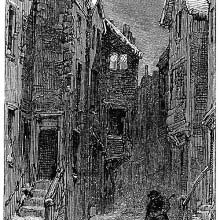 A man walks in the snow carrying a lantern along a narrow street