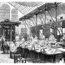 Silversmith's workshop where workers can be seen at a large collective workbench