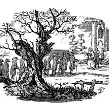 A tree in the foreground partly hides a funeral procession arriving at the church