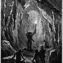 a man holds a torch at the entrance of a tunnel as others stand behind him