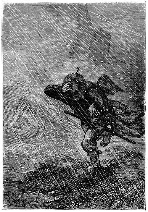 A man wearing a hat walks against the wind in a hail storm