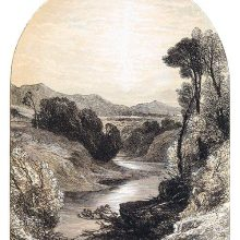 View of an open landscape with a river hemmed in by steep banks and hills on the horizon