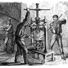 View of a workshop where two men are busy around a mobile press for molding goblets