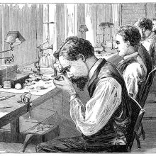 Workshop of a watch factory with men at work sitting on the chairs lining the workbench