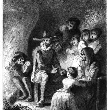 A group of people are gathered around a table near a fireplace