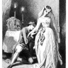 A man kneels beside a woman dressed as a bride and kisses her arm