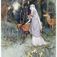 A young woman carrying a bunch of flowers walks in the woods followed by two deer