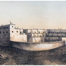 View of a pueblo with terraced structure and a semi-circular wall facing the viewer