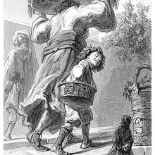 Gulliver stands on a street as a boy and his mother, carrying a tray on her head, pass him by