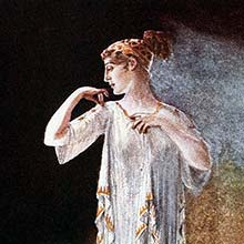 A woman stands against a strongly contrasted background wearing a dress in the Greek style