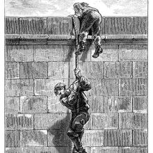A man climbs down on a rope from the top of a wall, followed by his companion