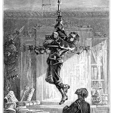 A man hangs on to a chandelier, thus pulling it down and uncovering an opening in the ceiling