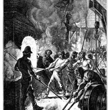 A puddler stands in front of a furnace, maneuvering the hook as a helper stays behind him