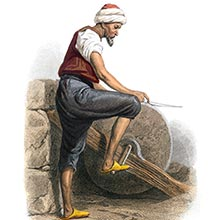 A man is seen from the side sharpening a knife on a grindstone operated by foot