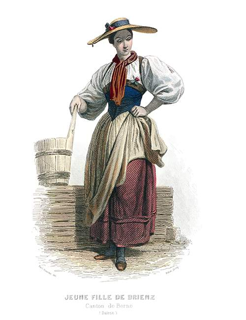 A Swiss girl in the traditional costume of Brienz stands looking down with one hand on her hip