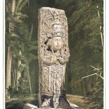 View of a Mayan stone idol standing against a background of woodland