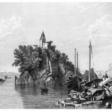 View of a rocky island on the Ganges, topped by a tower, with boats in the foreground