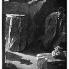 A man crouches at the bottom of a hut as the shadow of a man approaching can be seen on the ground