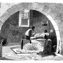 Two workers at a soap factory are seen through an arch crushing blocks of soda with shovels