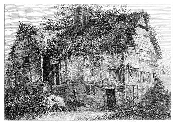 View of a picturesque and weather-worn cottage with a dilapidated thatched roof