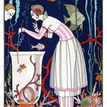 A woman leans over a tall fish-tank and teases the small fish swimming inside with a twig