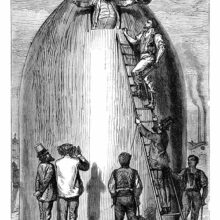A man appears through an opening at the top of a cannon shell-shaped rocket, greeted by his friends