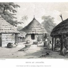 View of a group of huts in an African village, with local people sitting in the shade