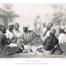 A group of men is sitting in a circle, having a discussion while onlookers stand at some distance