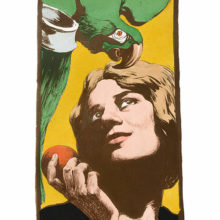 A woman is gazing up to the green parrot she's tempting with a fruit she holds in her hand