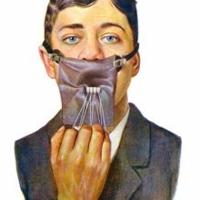 full face view of a young man wearing a rubber dental dam used to isolate four lower incisors