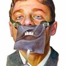 full face view of a young man wearing a rubber dental dam used to isolate four upper front teeth