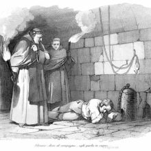 A prisoner chained to a post lies asleep on a cell floor, watched by two monks carrying torches
