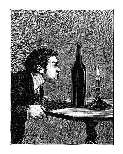 A man leans over a table with his cheeks puffed out to blow out a candle placed behind a bottle