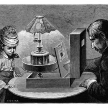 A girl and a man are seen at a table on which a praxinoscope theater has been placed