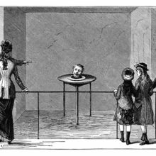 An small audience looks at a table on which the severed head of a man is staring back and talking
